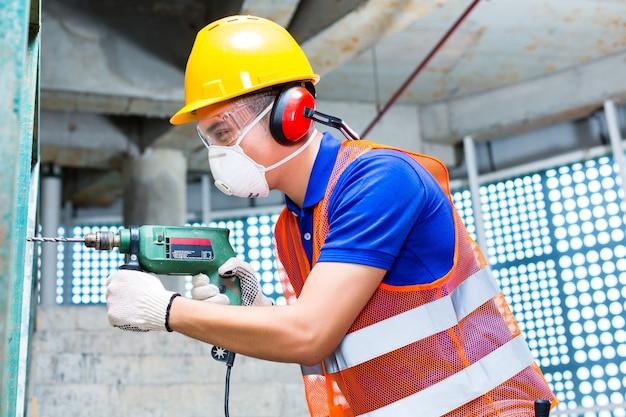 Azjatycki indonezyjski budowniczy lub robotnik budowlany wiercący maszyną lub wiertarką, ochronnikami słuchu, maską i kaskiem lub hełmem w ścianie budynku wieżowego