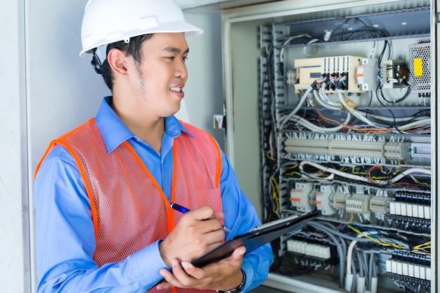Azjatycki indonezyjski technik lub elektryk wykonujący test działania skrzynki bezpiecznikowej lub skrzynki rozdzielczej z liniami energetycznymi na placu budowy lub w fabryce do odbioru
