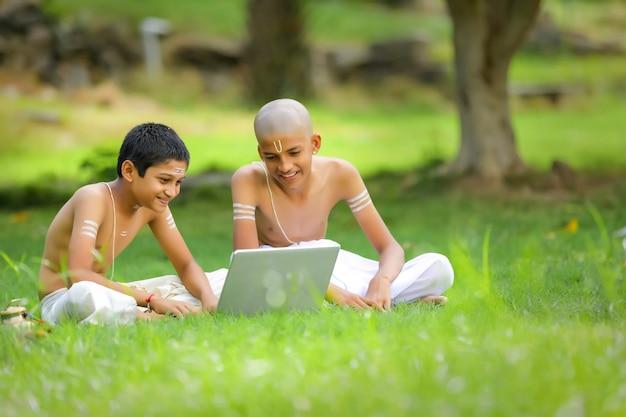Azjatycki / indyjski chłopiec uczący się na laptopie, koncepcja e-learningu, nauka w domu