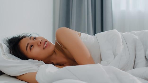 Azjatycki indyjski dama śpi w pokoju w domu. młoda azjatycka dziewczyna czuje się szczęśliwa relaksuje odpoczynek leżąc na łóżku, czuć się komfortowo i spokojnie w sypialni w domu rano.