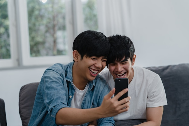 Azjatycki influencer para gejów vlog w domu. azjatyccy mężczyźni lgbtq szczęśliwi relaksują się, korzystając z technologii telefonu komórkowego, zapisują styl życia vlog wideo przesyłane w mediach społecznościowych, leżąc na kanapie w salonie.