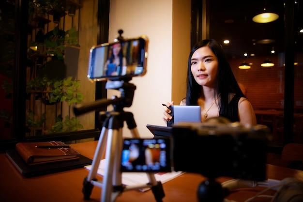 Azjatycki influencer w domu rozmawiający przed kamerą na vlogu