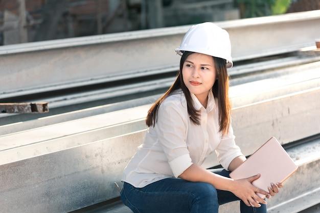 Azjatycki inżynier budownictwa z białą kask bezpieczeństwa odwiedzić budowę.
