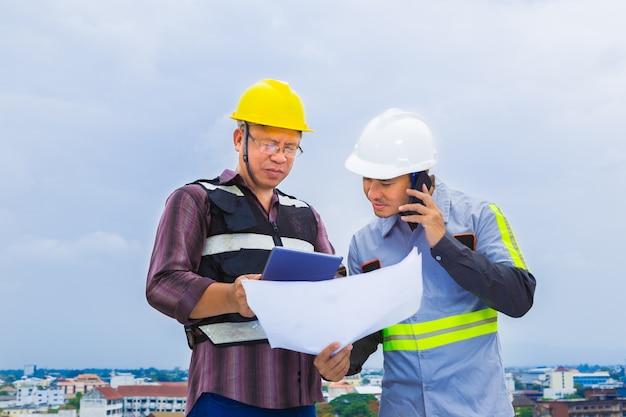 Azjatycki inżynier budowy pracy z brygadzistą podczas korzystania z jego telefon