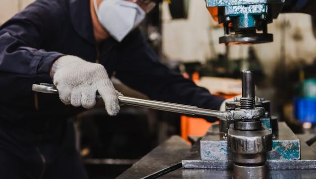 Azjatycki inżynier fabryczny w mundurze, kasku, rękawiczkach i masce na twarz ciężko pracuje w fabryce przy tokarce.