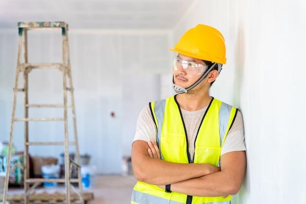 Azjatycki inżynier lub koncepcja biznesowa architektury i budownictwa - biznesmen lub architekt w kasku na placu budowy, budynek