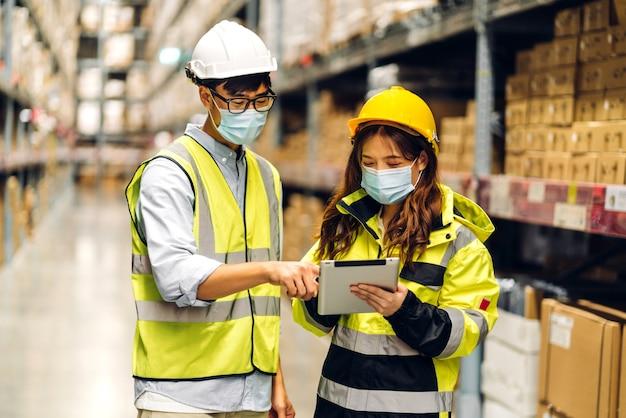 Azjatycki inżynier mężczyzna i kobieta w hełmach poddanych kwarantannie w związku z koronawirusem w masce ochronnej