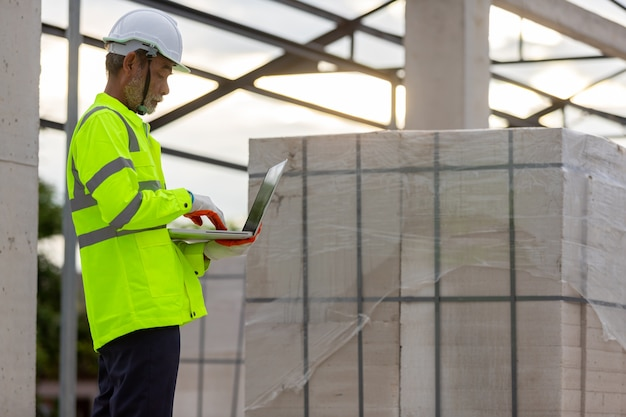 Azjatycki inżynier technik nadzorujący nadzór budowy przy budowie konstrukcji dachowych na budowie