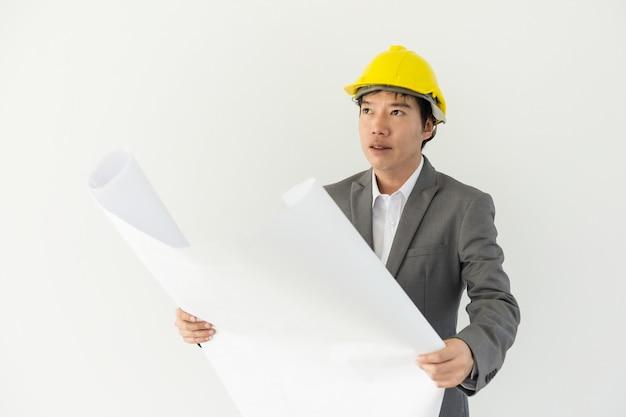 Azjatycki inżynier w żółtym kasku i oficjalnym mundurze trzymającym papier projektowy