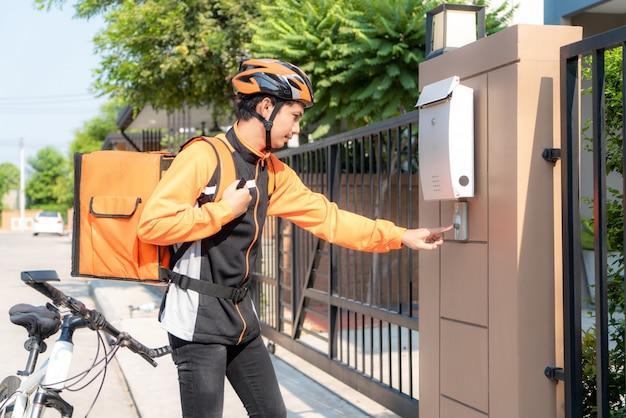 Azjatycki jeźdza doręczeniowy młody człowiek w pomarańcze mundurze z dostawy pudełkiem, roweru i dzwonienia klientów drzwiowy dzwon w przodu domu wiosce z kopii przestrzenią.