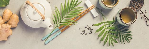 Azjatycki karmowy pojęcie - herbata i chopsticks na popielatym betonowym tle