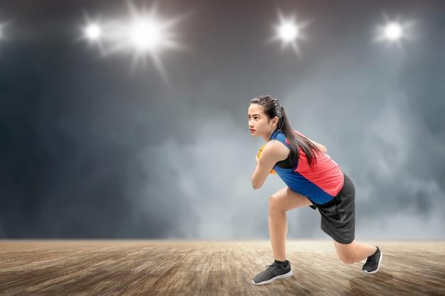 Azjatycki kobieta gracz koszykówki w akci z piłką