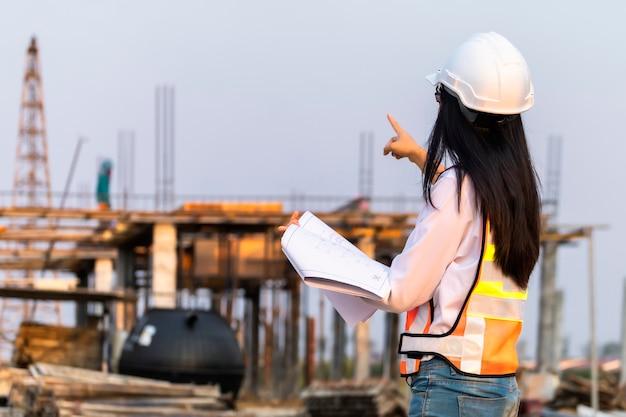 Azjatycki kobieta inżyniera budownictwa cywilnego papieru planu budynku architekt jest ubranym białego zbawczego hełm