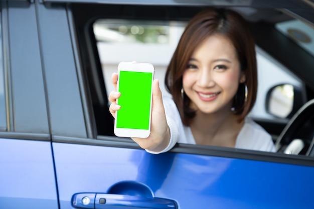 Azjatycki kobieta kierowcy obsiadanie w samochodzie i mienie telefon komórkowy z zieleń ekranem