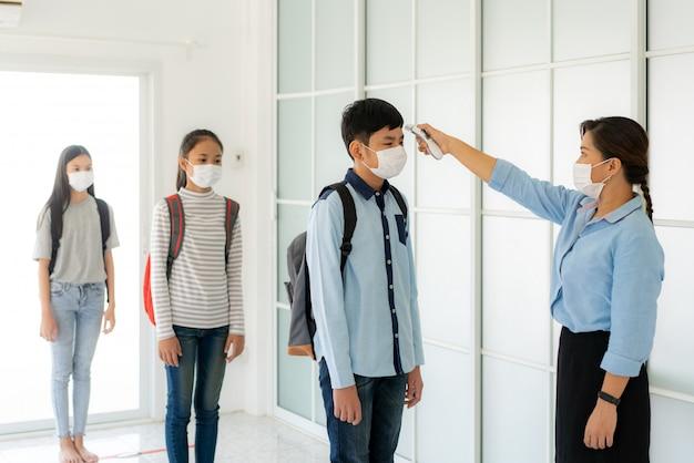 Azjatycki kobieta nauczyciel używa termometru temperatury przesiewania ucznia dla gorączki