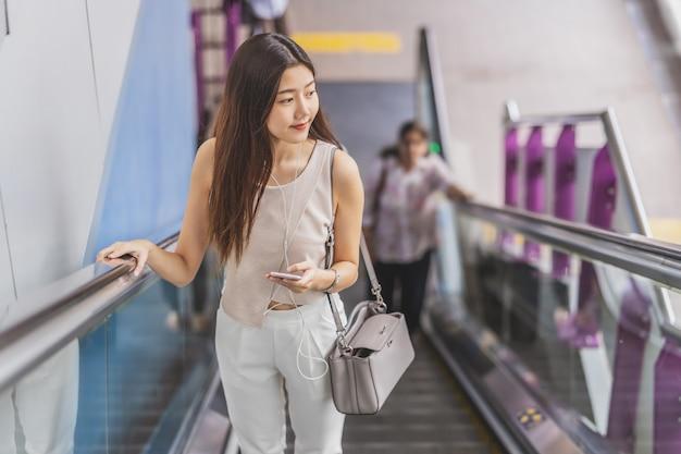 Azjatycki kobieta pasażer używa mądrze telefon komórkowego i chodzący w górę eskalatoru