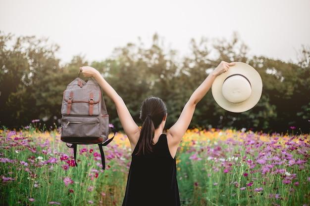 Azjatycki kobieta podróżnik z plecaka mienia kapeluszem, torbą i patrzeć zadziwiać ,.