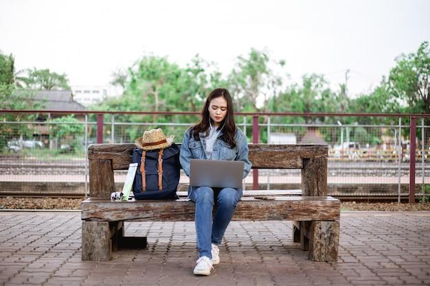 Azjatycki kobieta podróżnik z plecakiem, kapeluszem, mapą, okularami przeciwsłonecznymi, słuchawką i używać laptopem przy dworcem w wakacyjnym wakacje