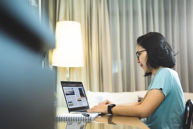 Azjatycki kobieta projektant pracuje na laptopie podczas gdy praca od domu przy nocą