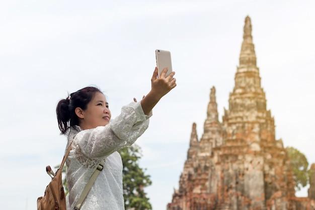 Azjatycki kobieta turysta z plecakiem bierze fotografię lub selfie z smartphone podczas podróży