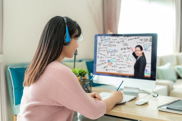 Azjatycki kobieta ucznia wideokonferencja e-learning z nauczycielem na komputerze w żywym pokoju w domu.
