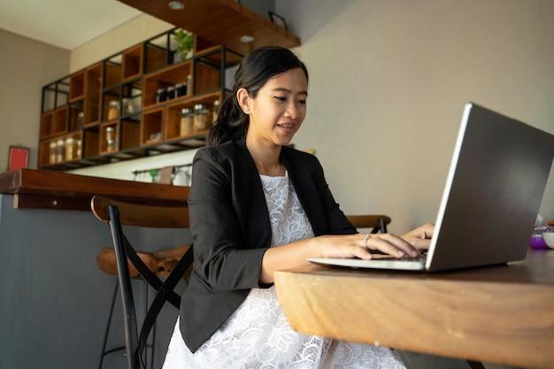 Azjatycki kobieta w ciąży obsiadanie używać laptop
