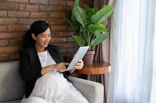 Azjatycki kobieta w ciąży siedzi i cieszy się pracujący używać pastylkę