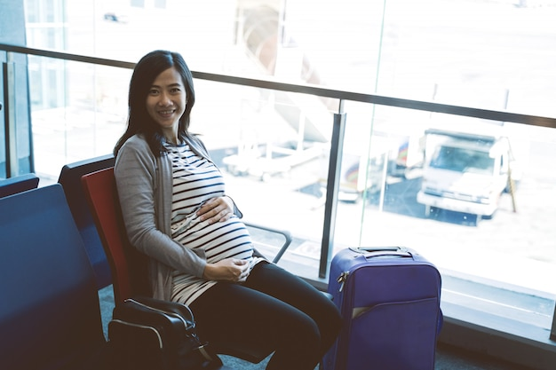 Azjatycki kobieta w ciąży siedzi obok walizki