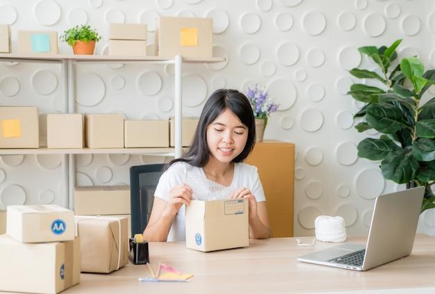 Azjatycki kobieta właściciel biznesu pracuje w domu z kocowania pudełkiem na miejscu pracy