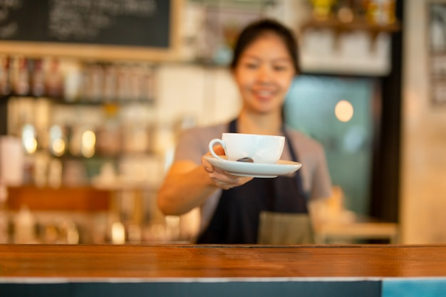 Azjatycki kobiety barista słuzyć filiżankę klient przy kawiarnią