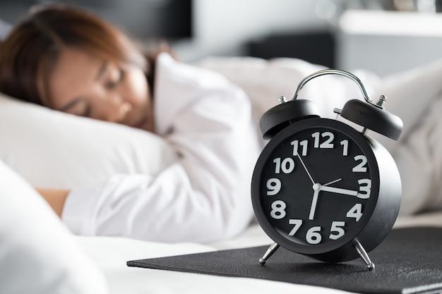 Azjatycki kobiety dosypianie na łóżku i budził się z budzikiem