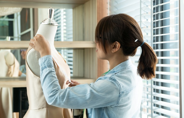 Azjatycki kobiety krawcowej projektant mody mierzy rozmiar manekin w sala wystawowej.