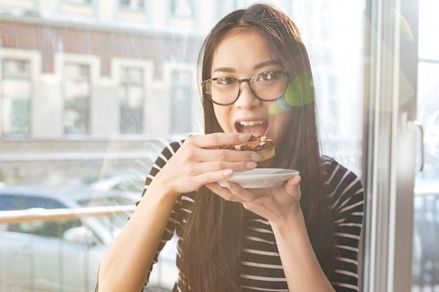 Azjatycki kobiety łasowania tort na parapecie