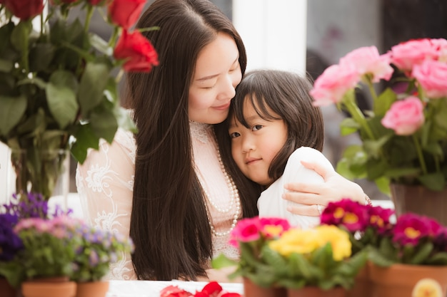 Azjatycki kobiety narządzanie kwitnie dla sprzedaży klienci w sklepie z jej córką