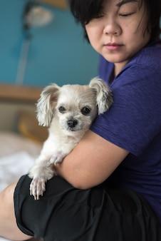 Azjatycki kobiety przytulenia pies w ten sposób śliczny na łóżku w sypialni
