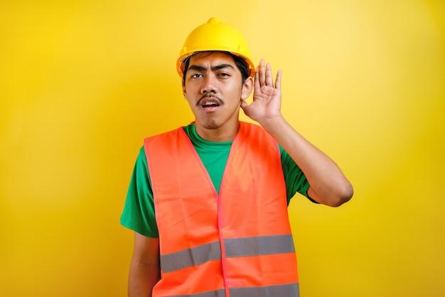 Azjatycki konstruktor mężczyzna ubrany w pomarańczową kamizelkę i kask ochronny na żółtym tle z ręką na uchu, słuchając przesłuchania plotek lub plotek. pojęcie głuchoty.