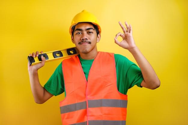 Azjatycki konstruktor pracownik człowiek z kask i kamizelka bezpieczeństwa trzymać waterpass na jego ramieniu z gestem zaufania. gotowa do pracy koncepcja na żółtym tle