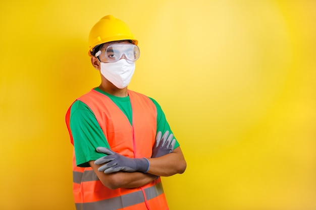 Azjatycki konstruktor pracownik pracownik noszący maskę i okulary ochronne stoi zgięty w ramię z gestem pewności siebie na żółtym tle