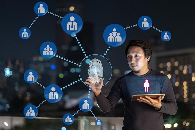 Azjatycki kreatywny freelancer korzystający z tabletu technologicznego z uwierzytelnianiem odciskiem palca i ar
