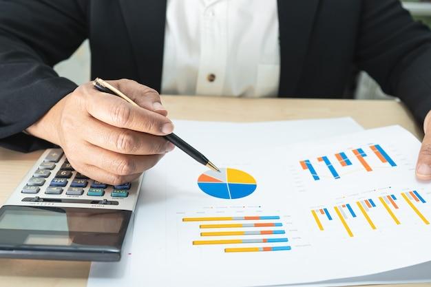 Azjatycki księgowy pracuje i analizuje raporty finansowe księgowość projektów z wykresem wykresu i kalkulatorem w nowoczesnej koncepcji biura, finansów i biznesu.