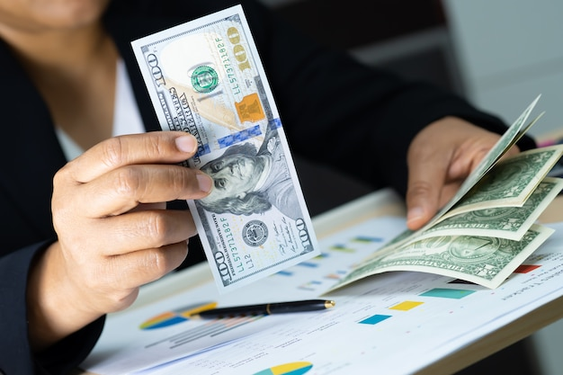 Azjatycki księgowy trzyma dolarowych banknoty w biurze