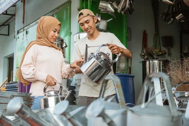 Azjatycki kupiec płci męskiej pokazujący tradycyjne czajniki kobiecie w welonie w sklepie ze sprzętem agd