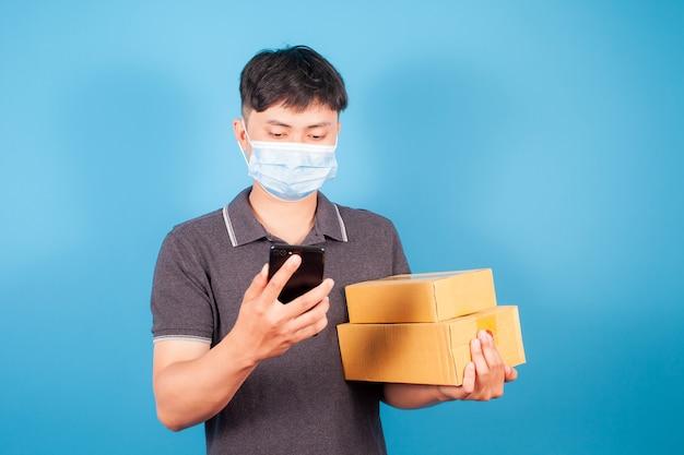 Azjatycki kurier internetowy, przewoźnik niosący pudełko i używający telefonu komórkowego do kontaktu z klientami, z których korzysta.