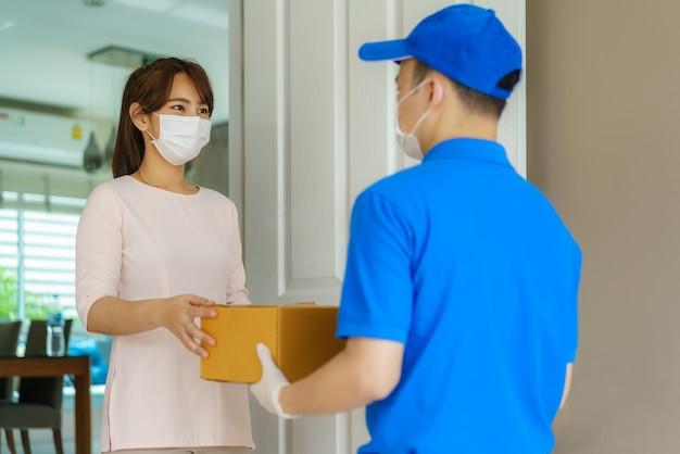 Azjatycki kurier w masce i rękawiczce w niebieskim mundurze trzymający kartonowe pudła przed domem i kobieta przyjmująca dostawę pudeł od kuriera podczas wybuchu covid-19.
