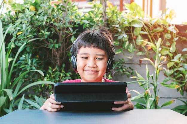 Azjatycki ładny chłopiec nosi bezprzewodowe słuchawki i uśmiecha się szczęśliwie podczas grania w gry na tablecie.