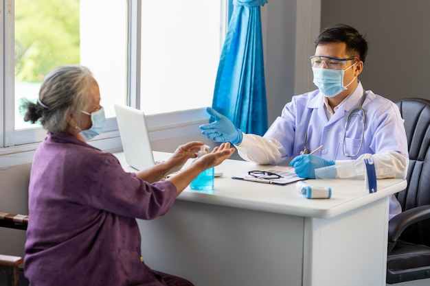 Azjatycki lekarz doradził starszej kobiecie, aby umyła ręce alkoholem przed zabiegiem, aby zapobiec początkowej infekcji wirusem koronowym.