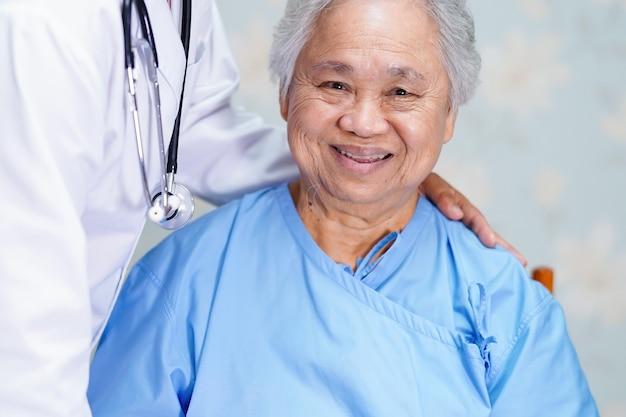 Azjatycki lekarz dotyka pacjenta azjatyckiego starszego kobiety z miłością.
