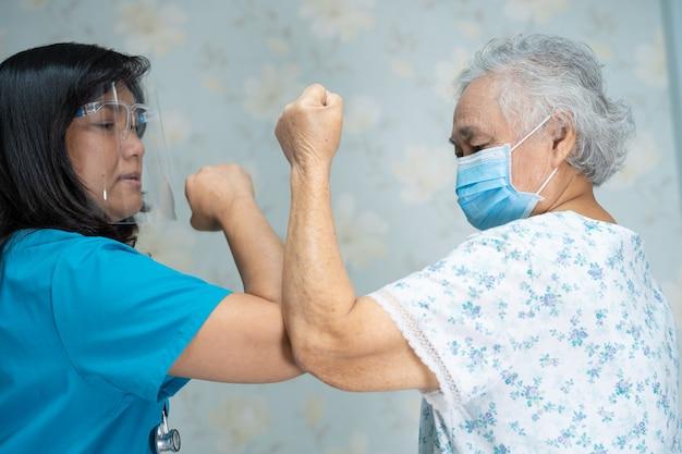 Azjatycki lekarz i starszy pacjent uderzają łokciami, aby uniknąć koronawirusa covid-19.