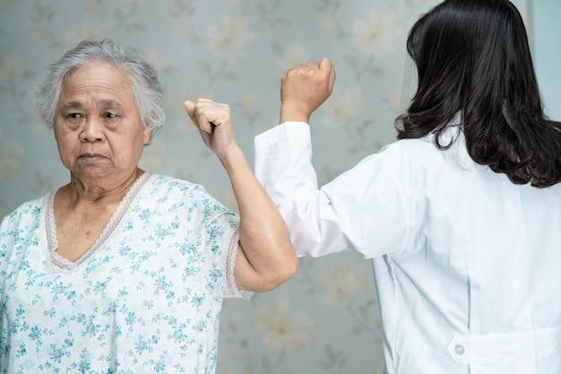 Azjatycki lekarz i starszy pacjent uderzają łokciami w celu zachowania dystansu społecznego, aby uniknąć koronawirusa covid-19.