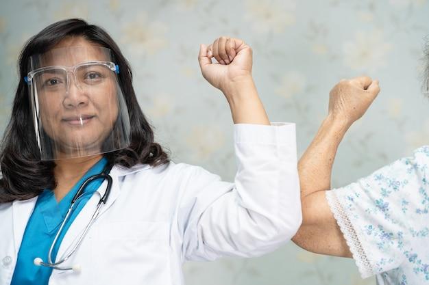 Azjatycki lekarz i starszy pacjent uderzają łokciami w celu zachowania dystansu społecznego, unikając covid-19.